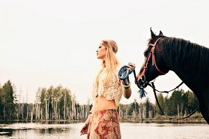 A young blonde woman wearing hippie-style clothes leading a horse by a lake