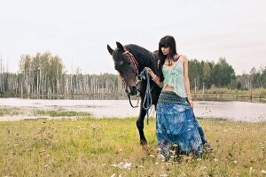A young, dark-haired woman wearing hippie-style clothes leading a horse by a lake