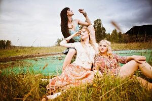 Three young woman in a meadow wearing hippie-style clothes