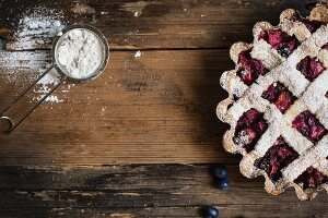 Blueberry tart with a lattice lid and icing sugar