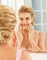Blonde Frau vor dem Spiegel trägt Reinigungsmilch im Gesicht auf