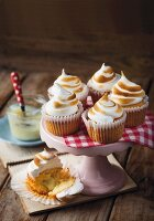 Lemon meringue cupcakes on and next to take stand