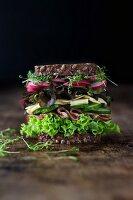 Hohes Sandwich mit Salat, Schinken, Käse, Gurken, Radieschen, Kresse und Vollkornbrot