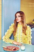 Junge Frau in gelber Spitzenbluse mit Rüschen sitzt am Tisch