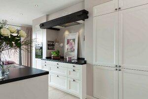 Offene Küche mit weißem Einbauschrank, daneben in Nische Küchenzeile mit integriertem Dunstabzug