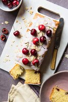 Cherry cake with icing sugar, fresh cherries and flaked almonds, sliced (seen from above)