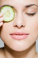 Frau bedeckt ein Auge mit einer Gurkenscheibe