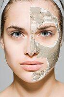 Junge Frau mit Gesichtsmaske auf einer Gesichtshälfte