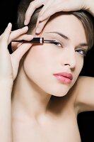 Junge Frau beim Auftragen von Eyeliner