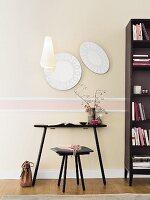 Elegante Wanduntergliederung mit Stuckleisten und pastellfarbenen Vliestapeten, davor schwarzer Tisch mit Hocker und Bücherregal