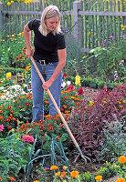 Junge Frau lockert mit einem Grubber die Erde