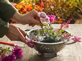 Gesteck aus rosa Herbstchrysanthemen in Küchensieb : 2/3