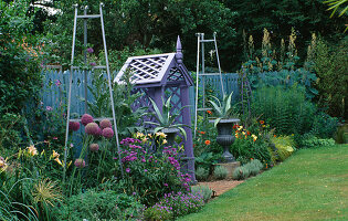 COVERED SEAT PAINTED Mauve SURROUNDED by Metal URNS PAINTED Silver with AGAVES, Silver Metal OBELISKS, ALLIUM CHRISTOPHII, HEMEROCALLIS, CARDOON AND ERIGERON. THE NICHOLS Garden