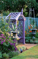 Mauve WOODEN SEAT with Silver PAINTED Metal URNS PLANTED with AGAVE. IN BORDER ARE ALLIUM GIGANTEUM, HEMEROCALLIS 'LUXURY LACE' AND ERIGERON 'AZURE FAIRY'. NICHOLS Garden, READING