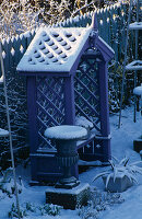 Purple COVERED SEAT FLANKED by Metal URNS AND BACKED by Blue DECORATIVE FENCING IN THE NICHOLS Garden at 69, ALBERT Road, READING, COVERED with SNOW
