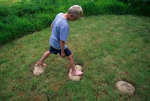 Designer Clare MATTHEWS: DINOSAUR FOOTPRINTS. Boy JUMPING Along CEMENT MOULDS of DINOSAUR FOOTPRINTS CUT INTO THE TURF