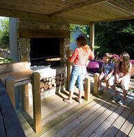 Designer Clare MATTHEWS: Devon GARDEN. OUTDOOR SEATING AREA AND OUTDOOR KITCHEN. Clare ABOUT TO PUT Pizza IN THE OVEN