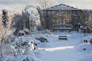Rosengarten mit Hecke, Laube und Bank im Schnee