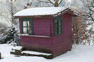 Rotes Gartenhaus mit grünen Fenstern im winterlichen Garten