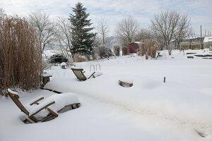Verschneiter Garten mit Liegestühlen, japanischen Steinlaternen, Miscanthus