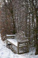 Verschneite Holzbank in Nische von Hecke aus Carpinus