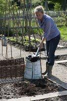 Frau bringt Pflanzerde zur Bodenverbesserung im Beet aus