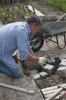 Mann legt Abrundung der Beeteinfassung aus Granit-Steinen