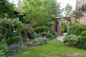Bepflanzter Garten mit Mauer und offenem Gartentor