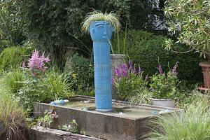 Getoepferte blaue Säule mit Kopf als Wasserspeier