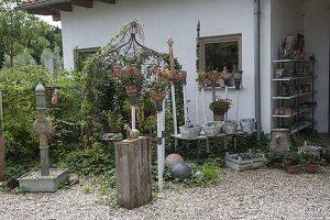Kies-Terrasse mit getoepferten Dekoelementen und Säule als Wasserspiel
