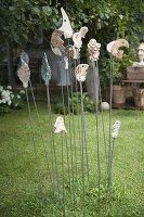 Getoepferte Gartenstecker auf Eisenstaeben