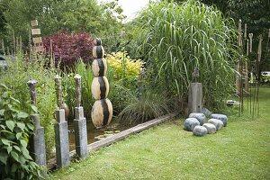 Garten mit getoepferten Kunstobjekten und Wasserspiel