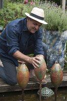 Herr Pluta installiert handgetoepfertes Wasserspiel