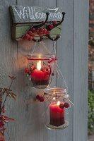 Alte Einmachgläser als Windlichter an Garderobenhake aufgehängt