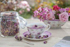 Rosentee in Tasse mit Rosendekor, Schale mit Blüten von Rosa