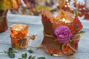Gläser umwickelt mit Blättern von Brombeere (Rubus) als Windlichter