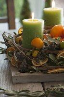 Mediterraner Adventskranz mit Olivenzweigen, schwarzen Datteln, Mandarinen