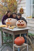 Familie schnitzt Kürbisse für Halloween
