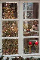 Blick von draussen ins weihnachtliche Zimmer mit Weihnachtsbaum