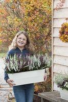 Mädchen trägt Metall-Jardiniere mit Calluna vulgaris Garden Girls