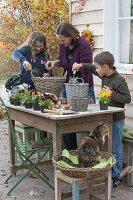 Mutter und Kinder bepflanzen Körbe mit Viola und Tulpenzwiebeln