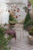 Weihnachtliche Terrasse mit kupfernen Kugeln am Zweig