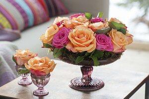 Gesteck aus Rosa (Rosen) mit Moos in flacher Schale mit Fuß und Gläschen