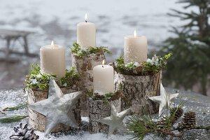 weiße Kerzen mit Moos auf Birkenstaemmen