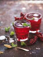 Red berry lemonade with ice and mint on vintage rusty metal backdround