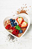 Healthy breakfast of muesli, berries with yogurt and seeds on white background