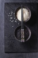 Black and white rice in old metal china bowls with black chopsticks over black slate background