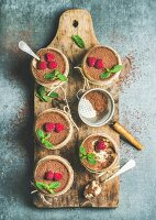 Tiramisu in glasses with mint leaves, fresh ripe raspberries and cocoa powder on rustic wooden board