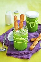 Creamy pea soup in glasses with pastry sticks