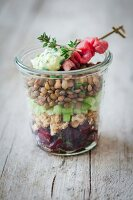 A lentil salad with roast beef and beetroot in a glass jar